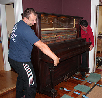 Professionals from TLC Moving and Storage moving a heavy piano safely